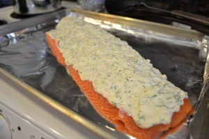 Spread the topping on the salmon.  It needn't go to the edge of the filet.